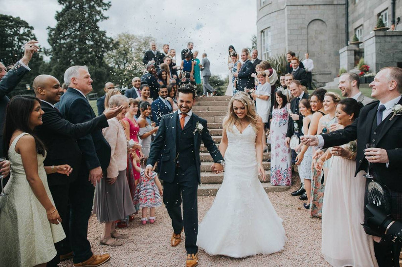 Bride and groom having confetti thrown over them by wedding guests