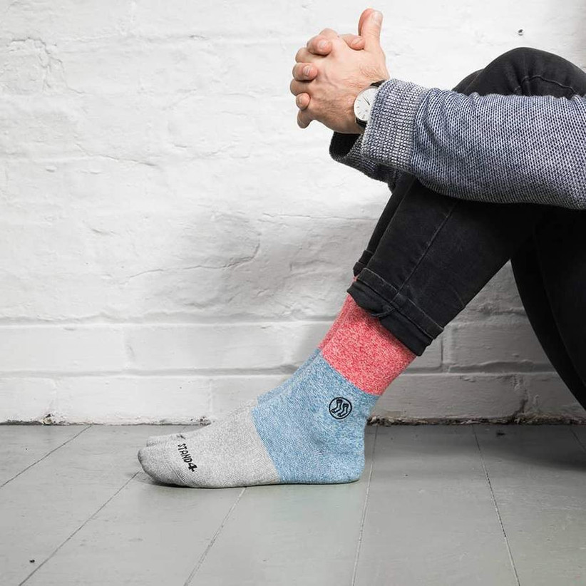 Man wearing red, blue and grey socks