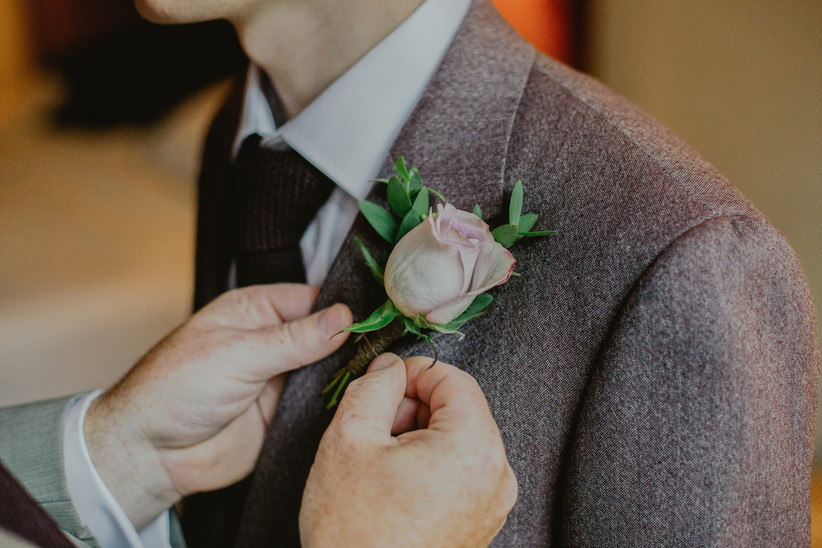 Groom getting his wedding buttonhole adjusted