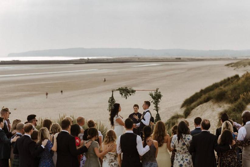 Bride, groom and guests at a coastal wedding ceremony