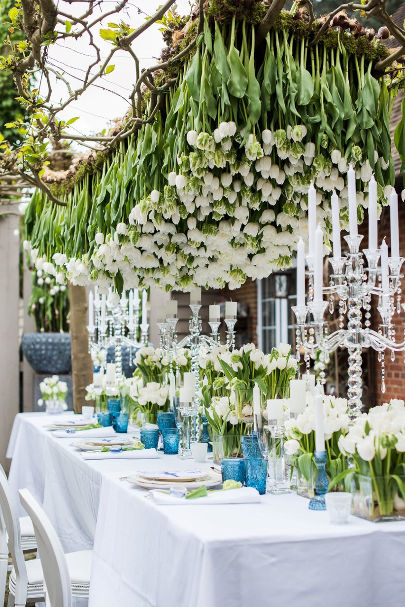 Hanging white tulips over a wedding dining table