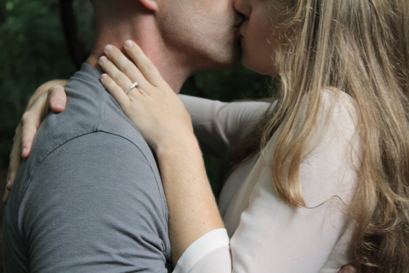 Couple kissing with engagement ring visible