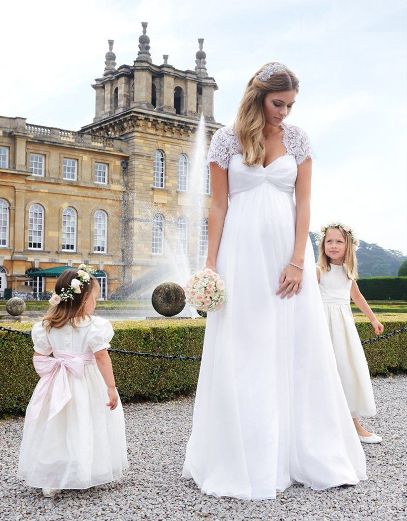 Model wearing long white maternity wedding dress with lace shoulders
