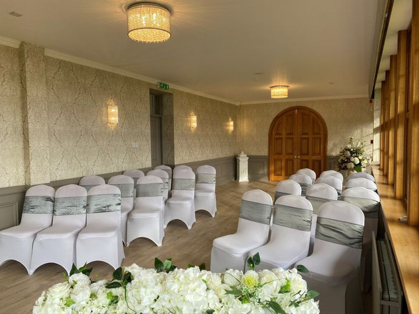 Wedding ceremony room with white chairs and flowers