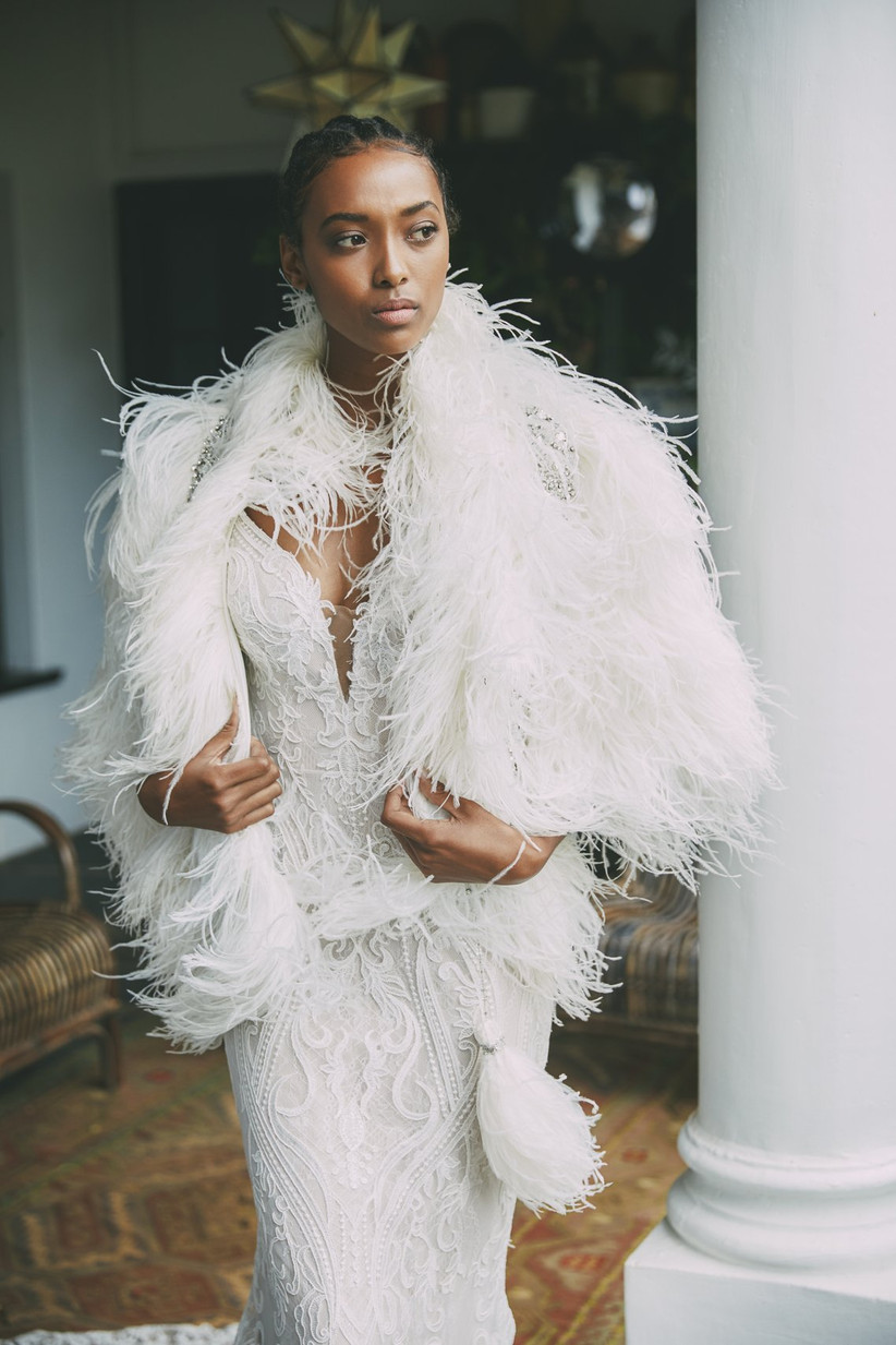 Model wearing a wedding dress and a feathered cape