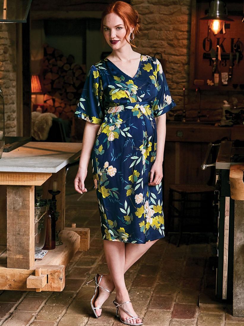 Pregnant model wearing a floral midi wedding guest dress
