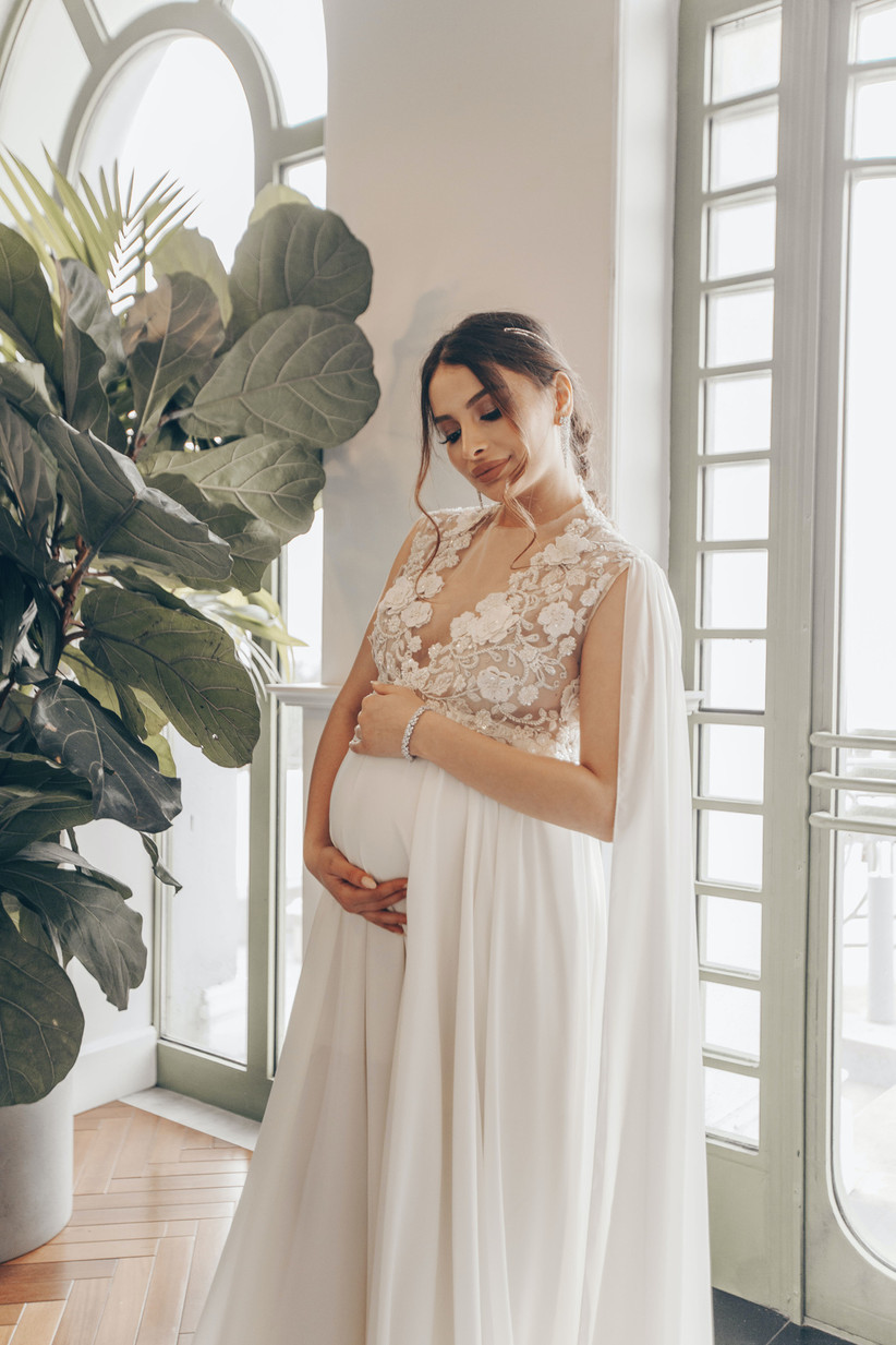 Pregnant bride cradling her bump in a flowing white gown