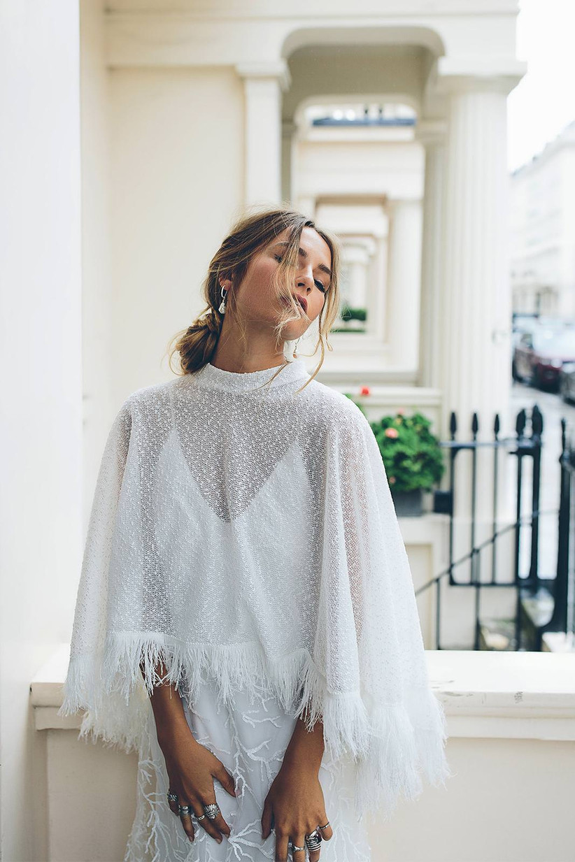 Model wearing a feather wedding cape