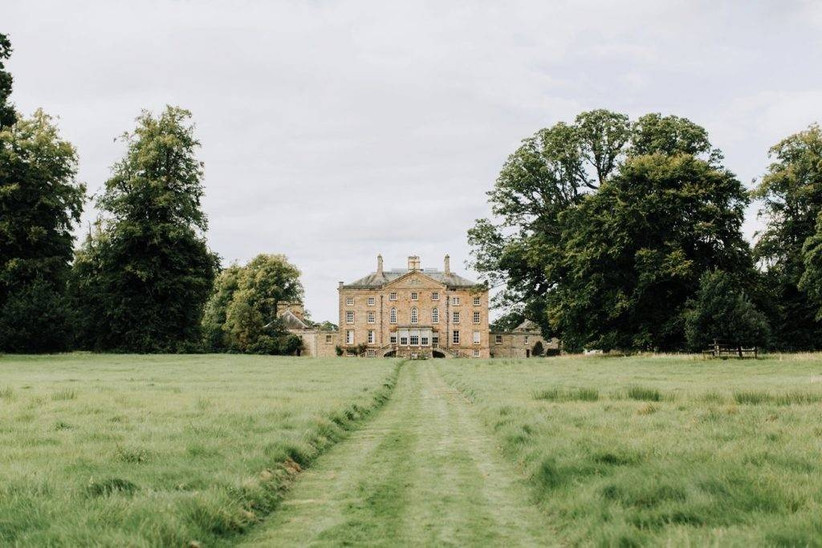 Grass path leading up to a country house wedding venue