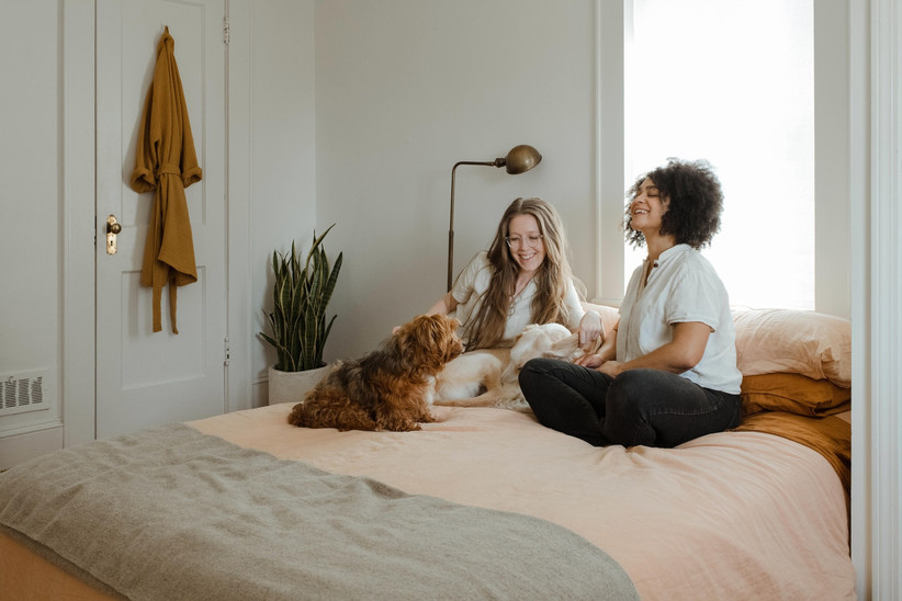 Female couple sit on a bed with a small furry dog