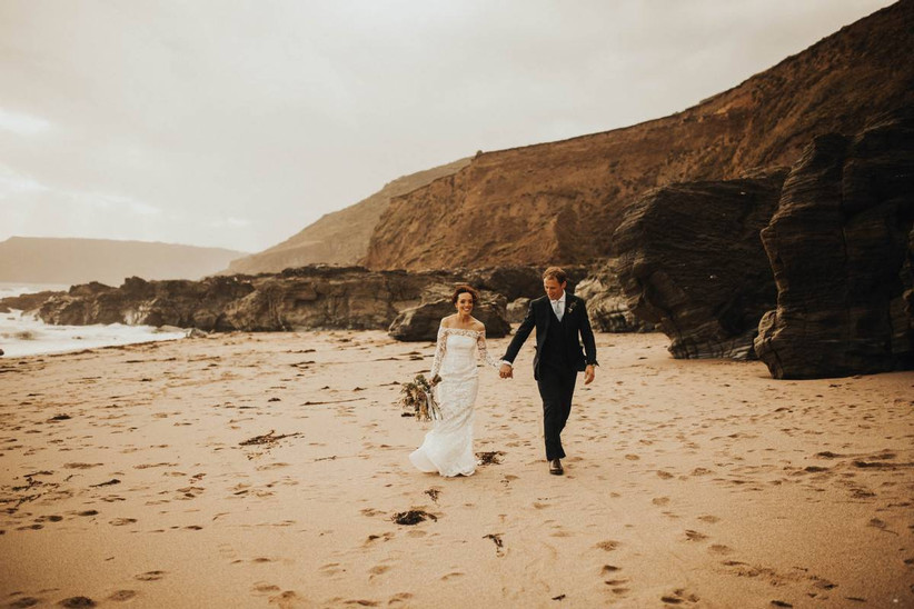 Bride and groom holding hands on a beach