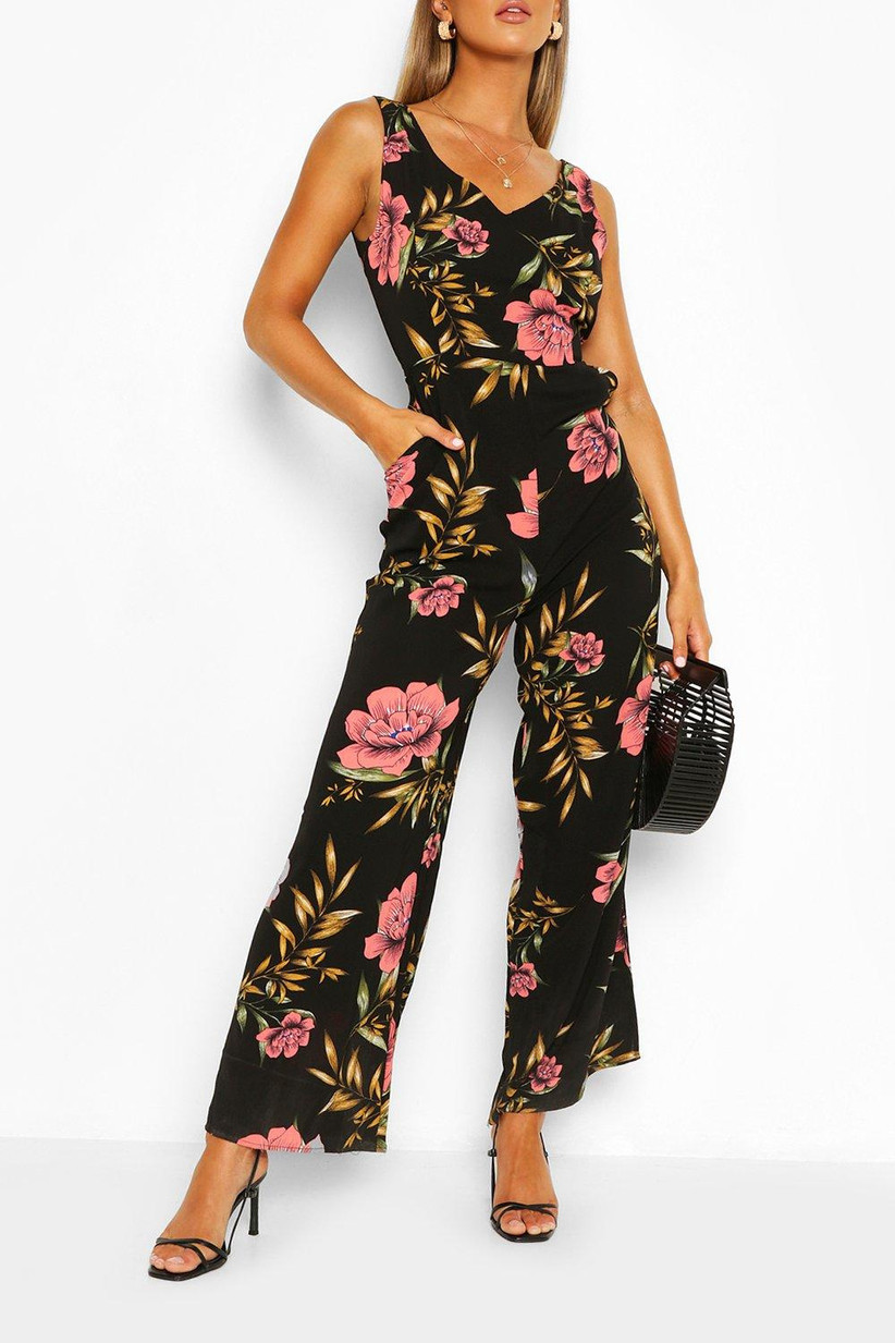 Model wearing a black jumpsuit with pink flower print