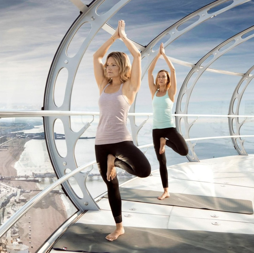 Two white blonde women in yoga kit doing tree pose on mats in a bubble above Brighton