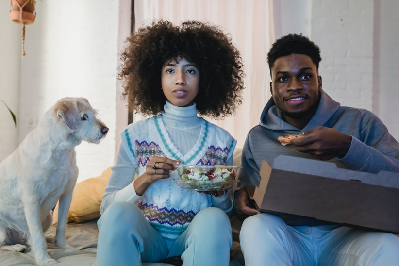 couple and a dog eating popcorn and pizza watching a film