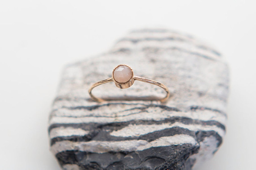 Peach moonstone engagement ring on a stone