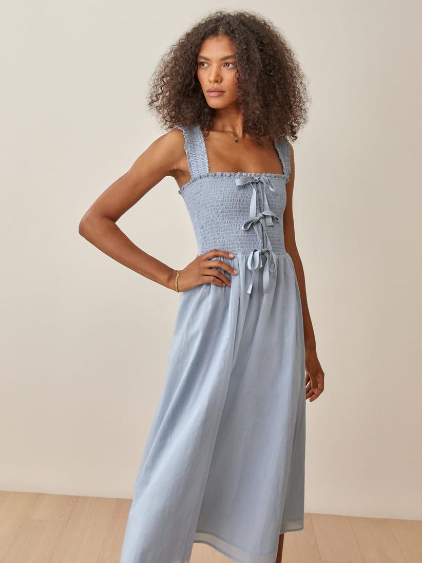 Model wearing a blue maxi wedding guest dress