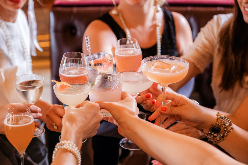 Group of white women clinking glasses containing pink and pale white cocktails