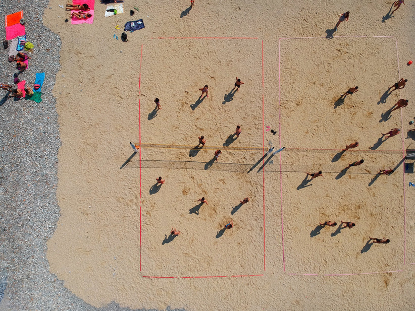 Aerial view of people playing on a beach volleyball court on the sand