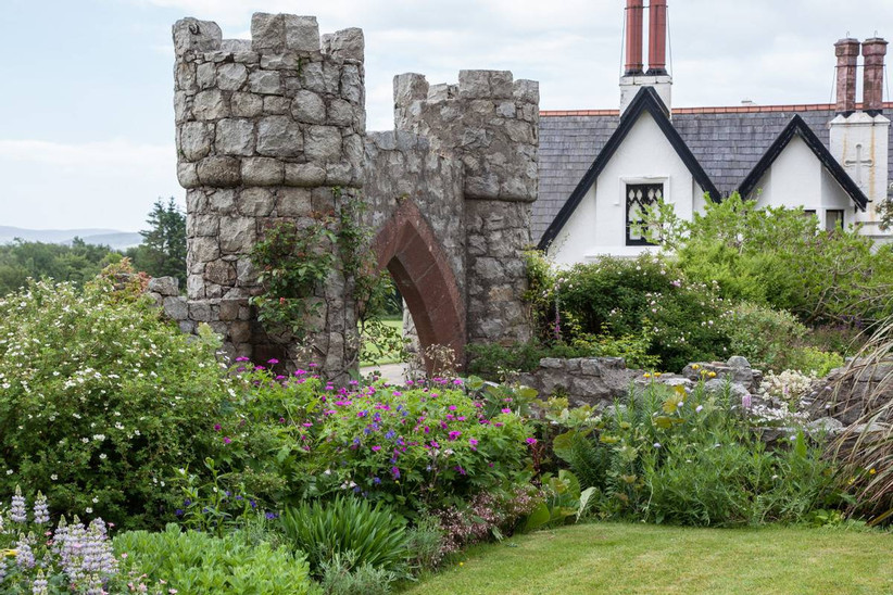 Gardens and a castle ruin next to a house