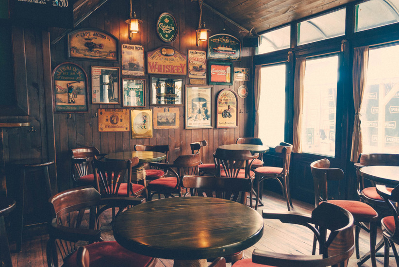Traditional pub interior with wooden walls, tables and chairs and old drinks signs as decoration