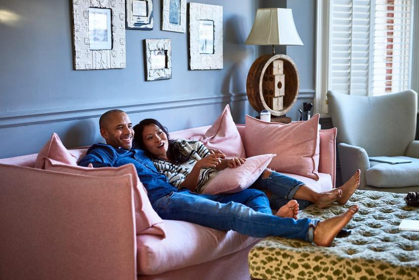couple sitting on pink sofa