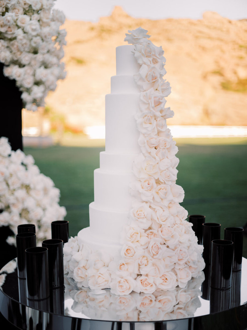 Tall white wedding cake with intricate rose details