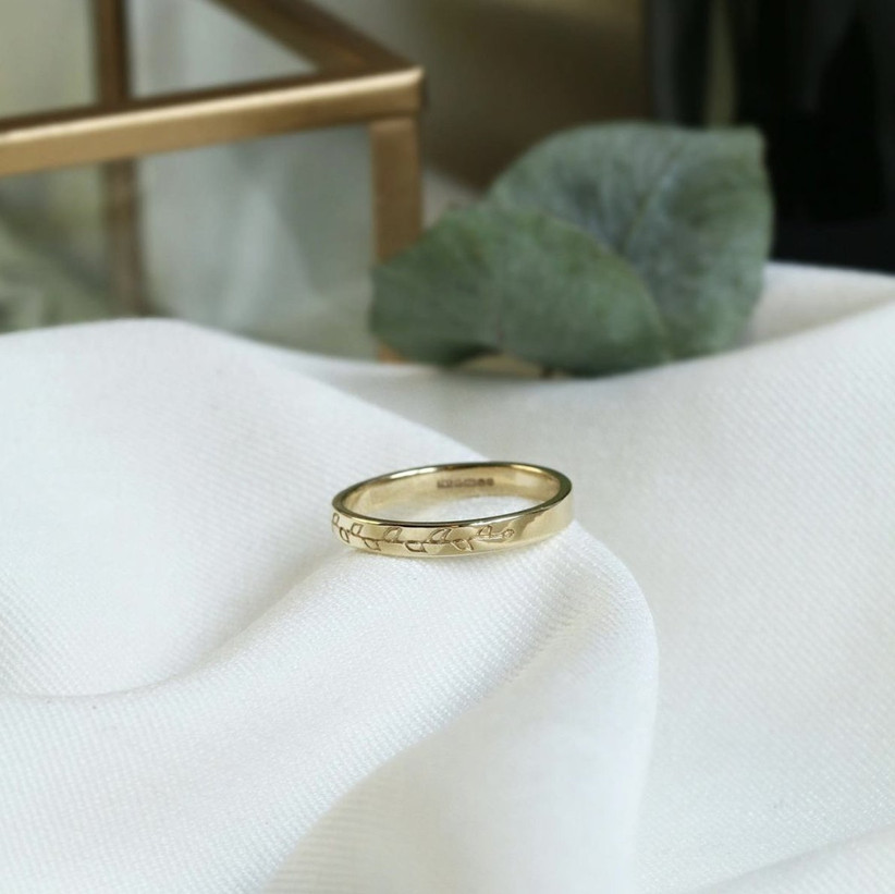 Gold evergreen commitment ring with an etched leaf design on a piece of white linen