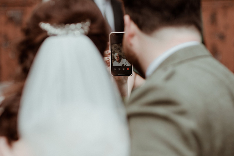 Backwards shot of a bride and groom FaceTiming a white man in a shirt on a smartphone