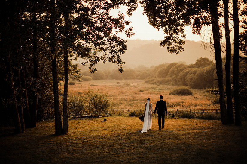 Bride and groom walking hand in hand in the countryside by fforest farm