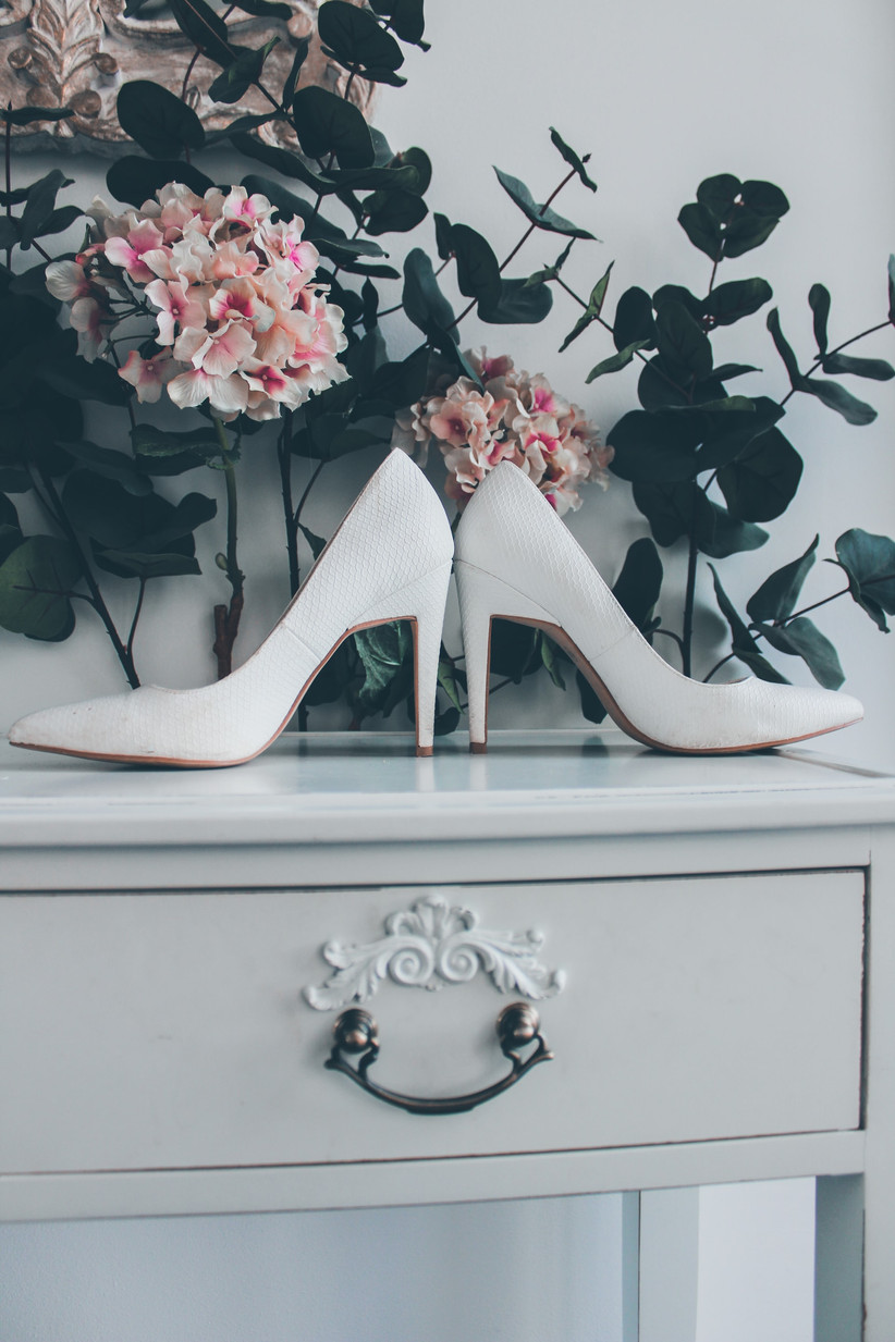 A pair of white high heels back to back