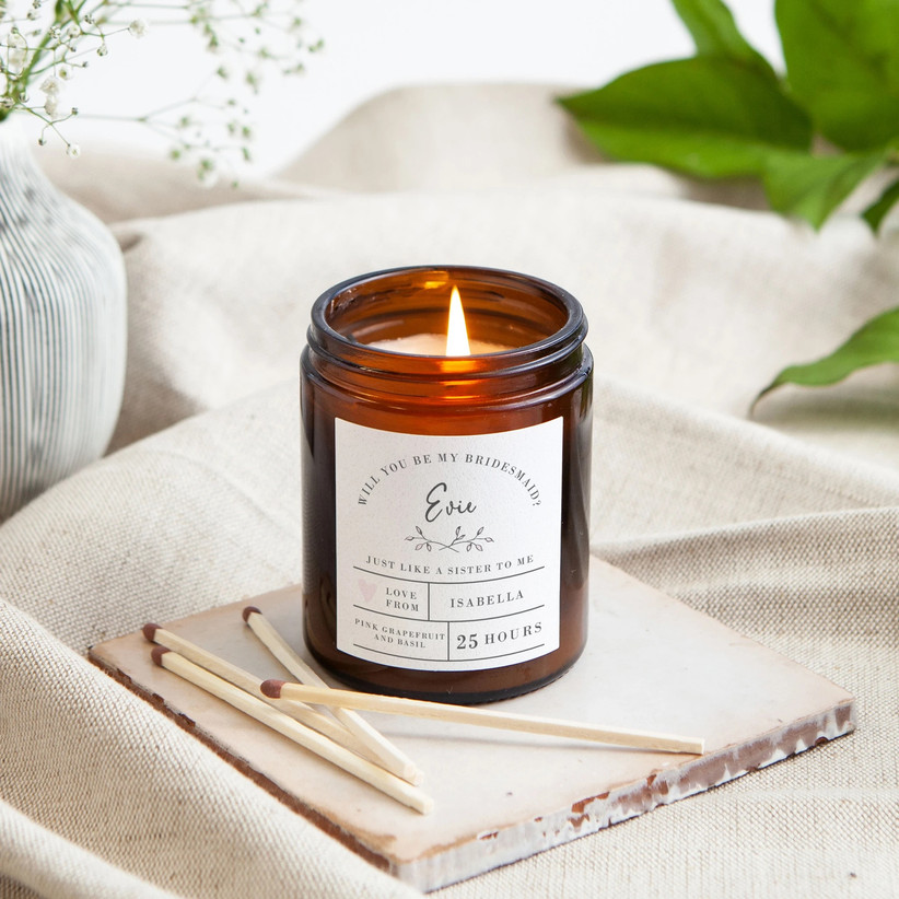 Candle burning in an dark brown glass jar with a personalised illustrated will you be my bridesmaid label