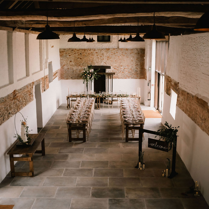 Interior of Curds Hall Barn dressed for a wedding reception with two long tables and flowers