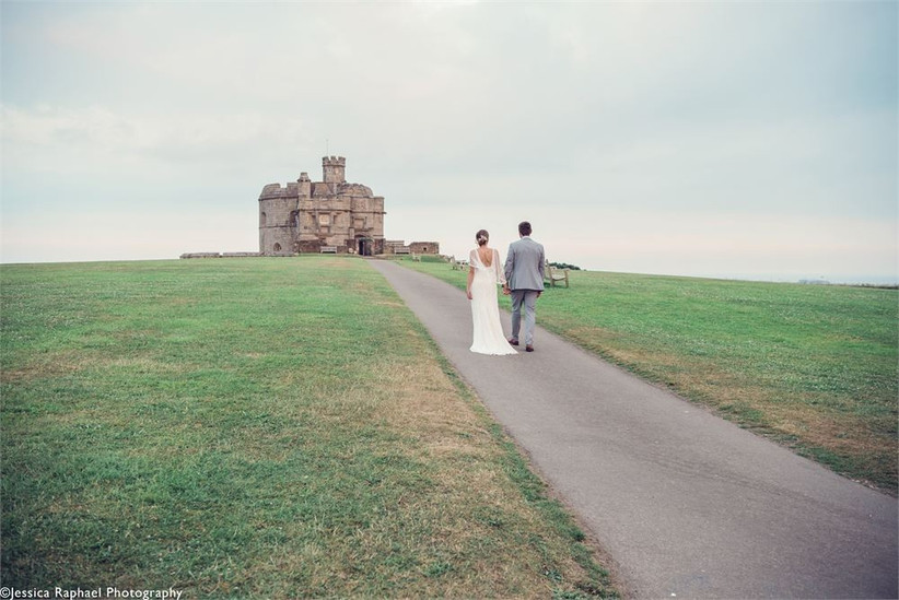 Bride and groom holding hands walking up a path to a castle