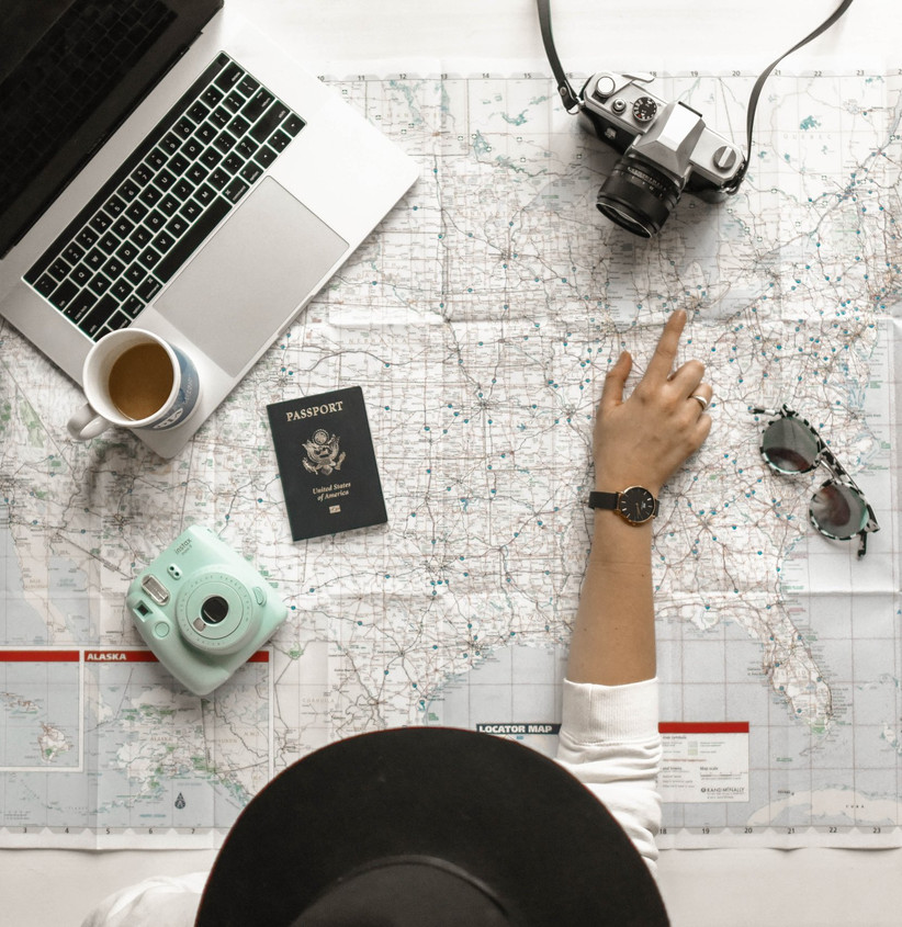 Woman wearing a black trilby hat planning a holiday on a map with a passport, polaroid camera, retro camera, cup of tea, sunglasses and laptop spread on the table in front of her