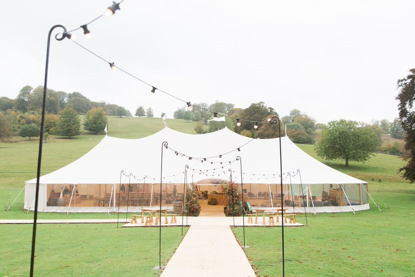 White sperry tent in a green field surrounded by countryside