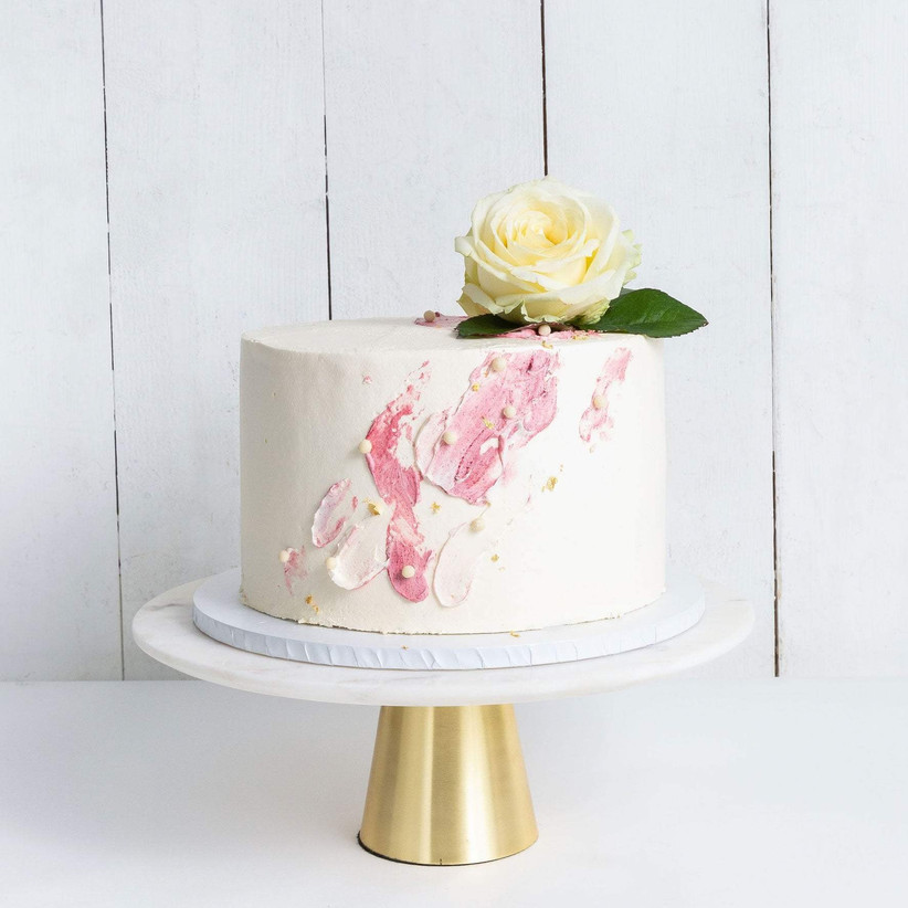 One-tier white wedding cake with pink detail