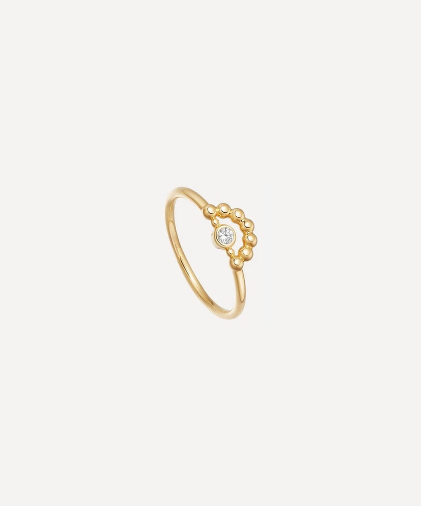 Thin gold ring with a small round white sapphire at it's centre and a beaded gold arc above it