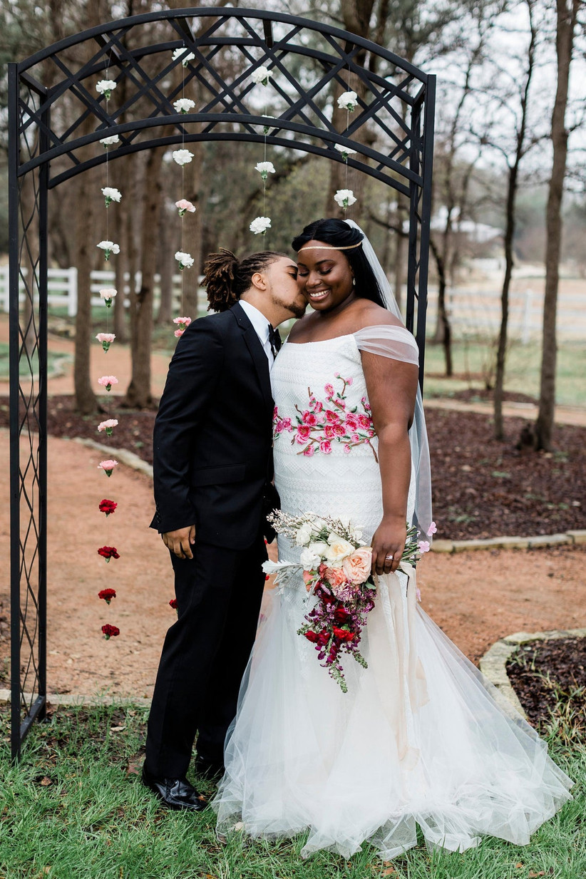 Bride and groom stand together in a park