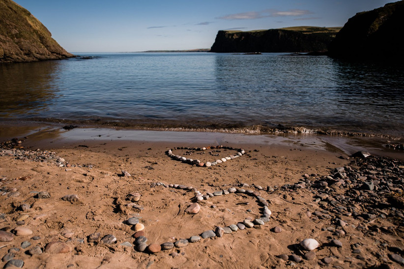 Two hearts made of pebbles on the empty beach
