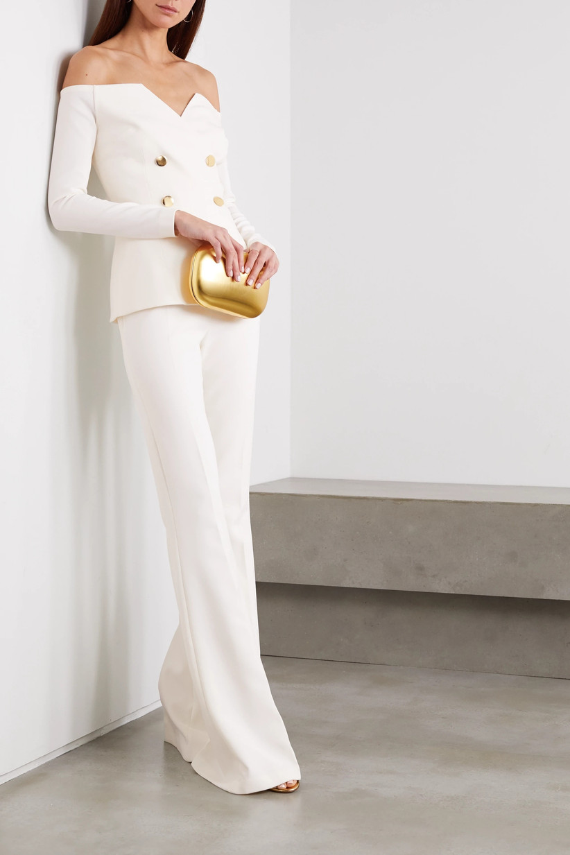 Girl wearing a Bardot tailored top with trousers and a gold clutch bag