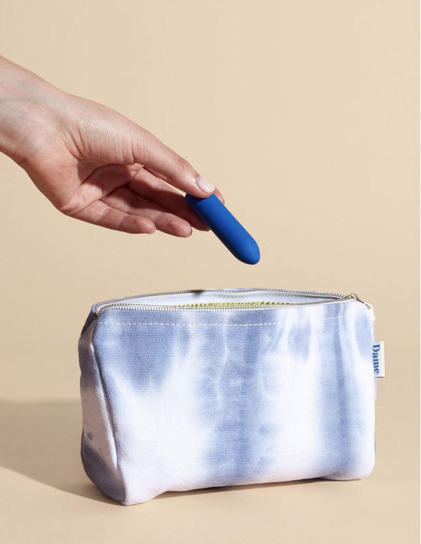A woman putting a bright blue bullet vibrator into a tie dye blue wash bag