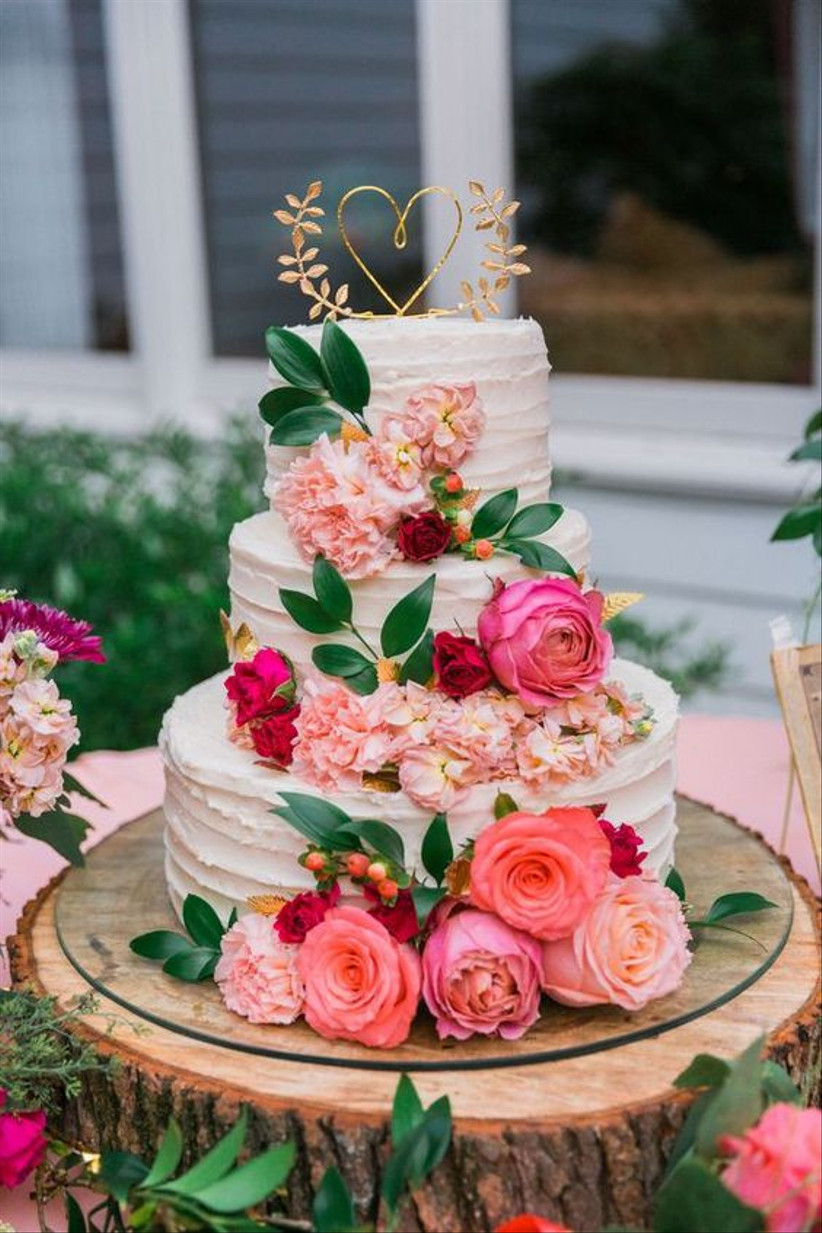 Three tiered textured buttercream rustic wedding cake with pink and red roses