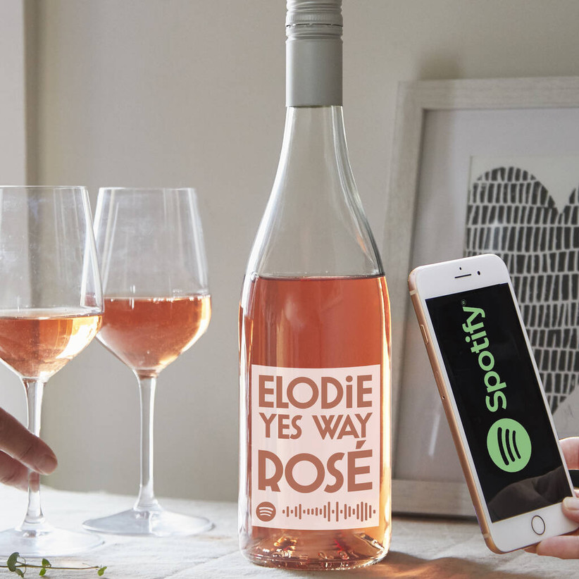 Bottle of rose wine with a personalised label and phone with an open Spotify app
