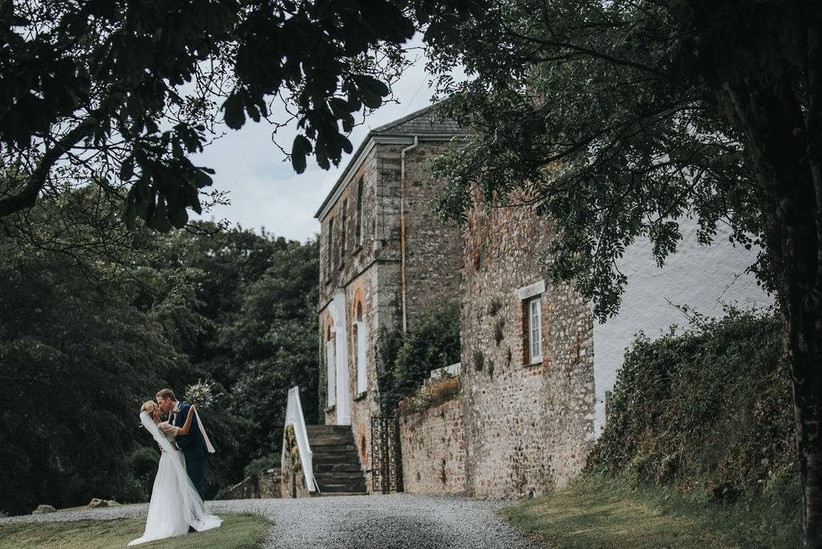 Stone building with couple outside kissing