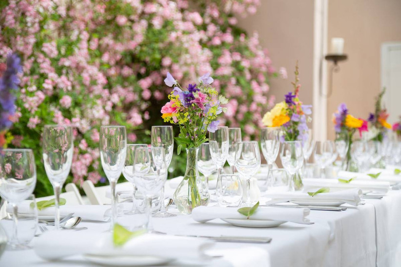Dining table decorated with bright flowers in vases