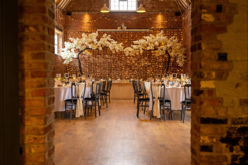 Brick walled dining area with white floral head table