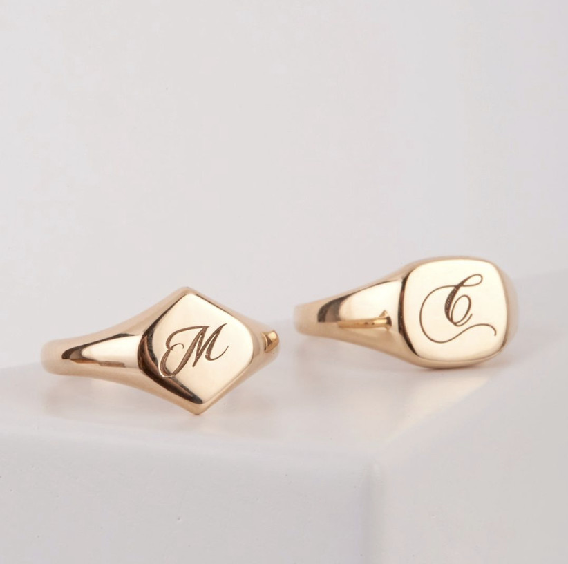 Two golden signet rings side by side, one in a diamond shape with an M initial and the other with a square shaped face and a C initial