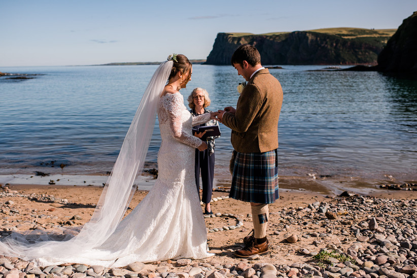 Caitlin and Stephen saying their vows on a beach