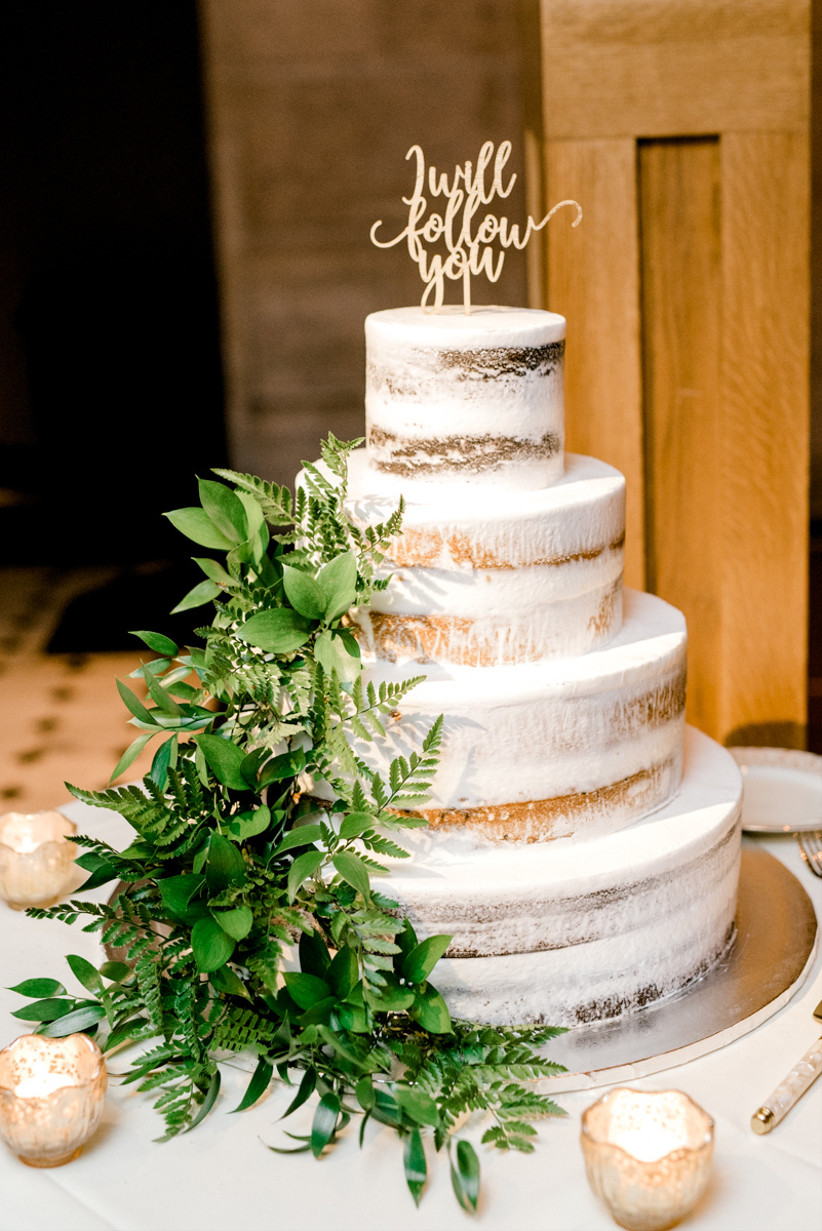 Four tiered semi naked rustic wedding cake with green foliage