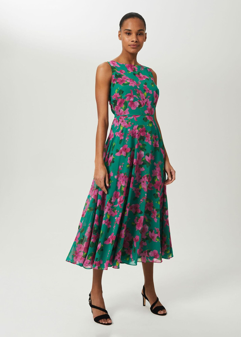 Girl with a sleeveless green dress with pink floral pattern